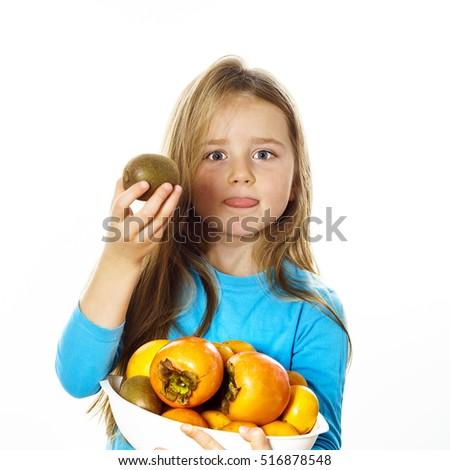 Cute little girl with plate of fruits: kiwi, date plum, mandarins, etc., isolated on white background