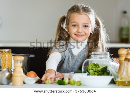 Cute little girl with ponytailes cooking Brussels sprouts in kitchen - stock photo