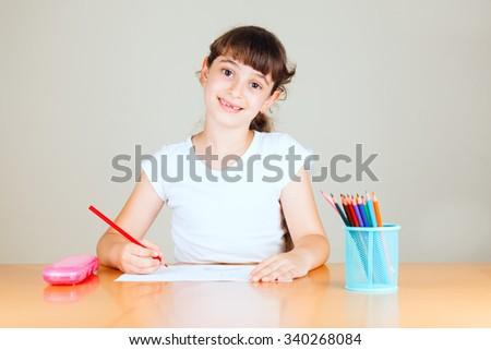 Cute little girl with red sketch pen is drawing at kindergarten - stock photo