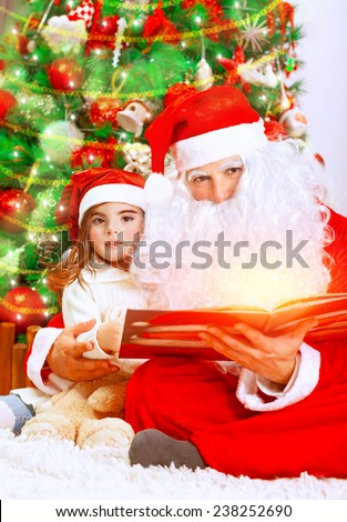 Cute little girl with Santa Claus sitting near Christmas tree and reading Magic xmas story, fairy tale, cozy festive eve at home - stock photo
