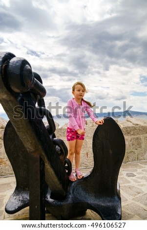 Cute little girl with ship anchor on the seaside, stormy weather