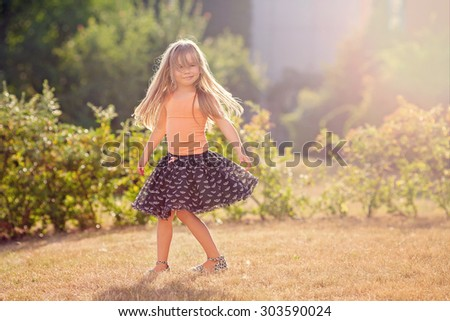 Cute little girl with skirt, dancing and swirling around, summertime outdoors - stock photo