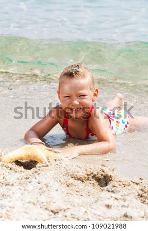 Cute Little girl with starfish on the beach
