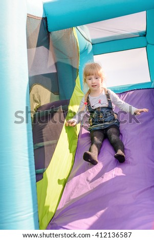 Cute little girl with static electrically charged hair sliding down onto landing for blue, green and purple inflatable outdoor carnival amusement ride