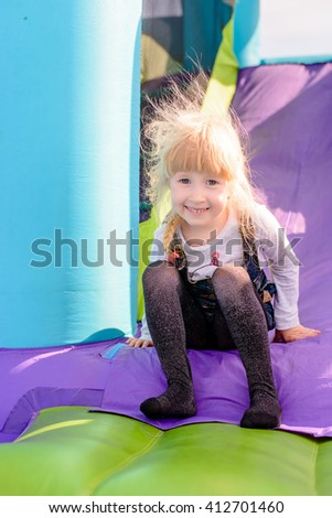 Cute little girl with static electrically charged hair sliding down onto landing for blue, green and purple inflatable outdoor carnival amusement ride - stock photo