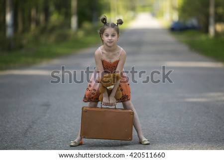Cute little girl with suitcase and Teddy bear is on the road. - stock photo
