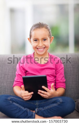 cute little girl with tablet computer at home - stock photo