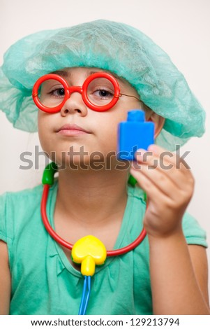 Cute little girl with toy glasses and a doctor's costume holds a toy stethoscope and toy bottle of medicine - stock photo