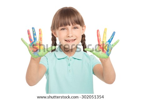 Cute little girl with two braids is isolated on white background. Girl looking at camera, cheerfully smiling and showing soiled in paint hands - stock photo