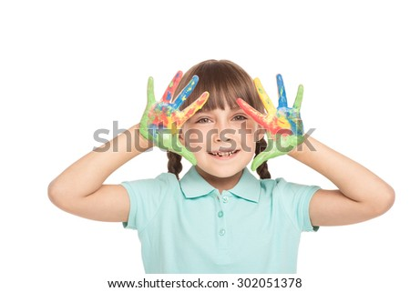 Cute little girl with two braids is isolated on white background. Girl with soiled in paint hands looking at camera and cheerfully smiling - stock photo