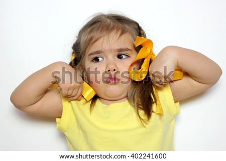 Cute little girl with yellow bows and yellow T-shirt showing strong fists over white background, sign and gesture concept - stock photo