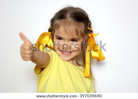 Cute little girl with yellow bows and yellow T-shirt showing thumb up gesture over white background, sign and gesture concept - stock photo