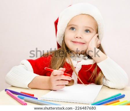 Cute little girl writes letter to Santa  - stock photo