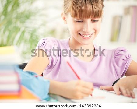 Cute little girl writing her homework. - stock photo