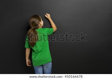 Cute little girl writing in a blackboard, with copy space.