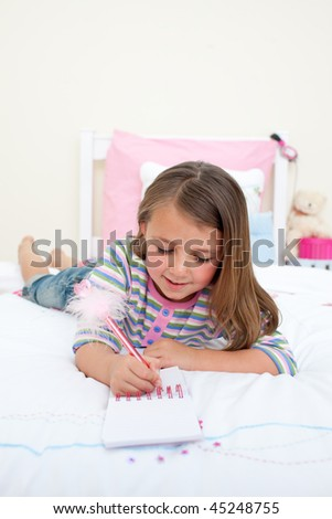 Cute Little girl writing on a notebook lying on her bed - stock photo