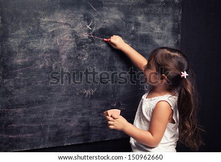 cute little girl writing something with a pink chalk on blackboard - stock photo