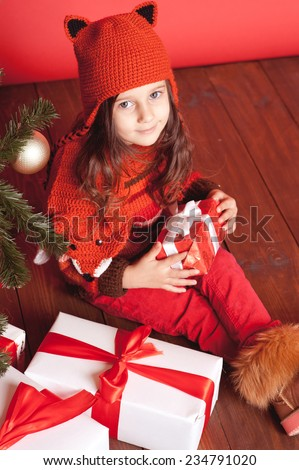 Cute little girl 4-5 year old sitting on wooden floor with christmas presents in room. Looking at camera. Wearing trendy knitted hat and scarf.  - stock photo
