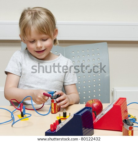 Cute little girl (5 years old) doing experiments with electricity