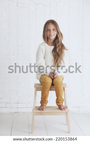 Cute little girl 8-9 years old wearing knit trendy winter clothes posing over white brick wall - stock photo