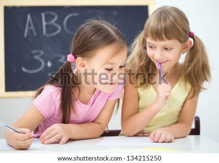 Cute little girls are writing using a pen in preschool - stock photo