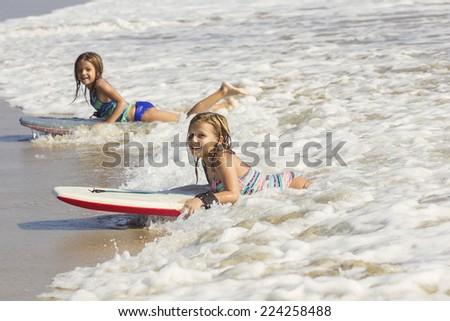 Cute little girls boogie boarding in the ocean waves - stock photo