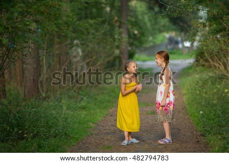Cute little girls excitedly talking in the Park.