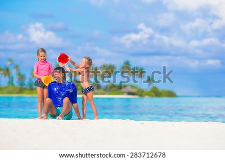 Cute little girls having fun with dad on white beach