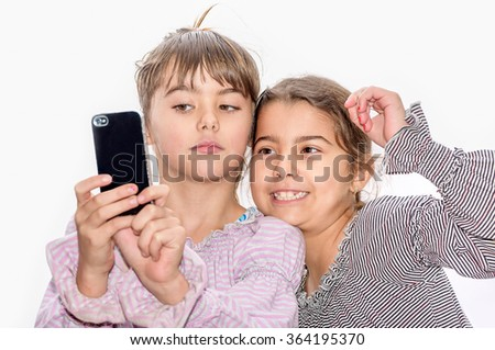 Cute little girls making selfie with mobile phone on the white background - stock photo