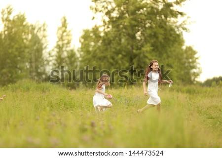 Cute little girls running around on the field - stock photo