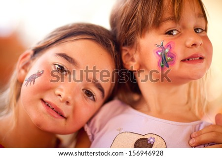 Cute Little Girls Showing Their Face Painting At A Party.