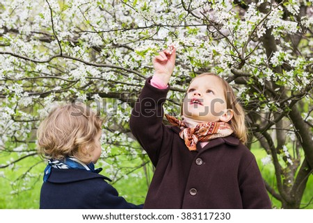 Cute little girls (sisters 3 and 4 years old) near flowering trees. - stock photo