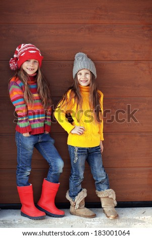 Cute little girls wearing knit winter clothes posing over wooden background - stock photo