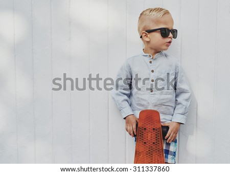Cute little guy in big trendy sunglasses that he has borrowed from his mother or father posing with his skateboard against a white wooden wall with copyspace - stock photo