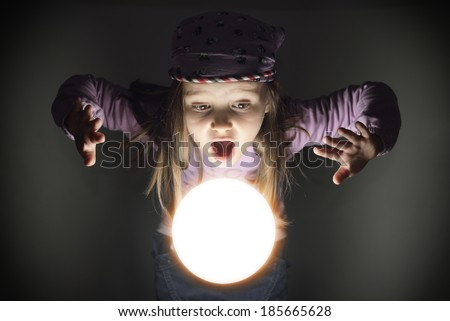 Cute little gypsy girl amazed over a glowing crystal ball, seeing the future - stock photo