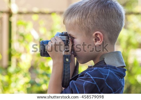 Cute little happy boy with vintage photo camera outdoors - stock photo