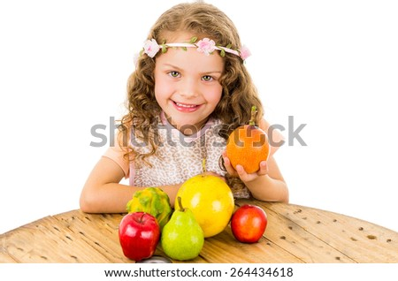 Cute little happy preschooler girl with fruits on the table isolated on white - stock photo
