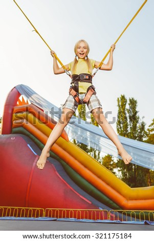Cute little happy smiling girl jumping on a rubber at summer theme park - stock photo