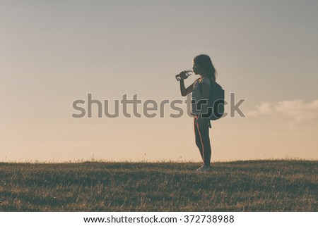 Cute little hiker girl drinking water and resting.Image is intentionally with grain and toned.Refreshment for little hiker - stock photo