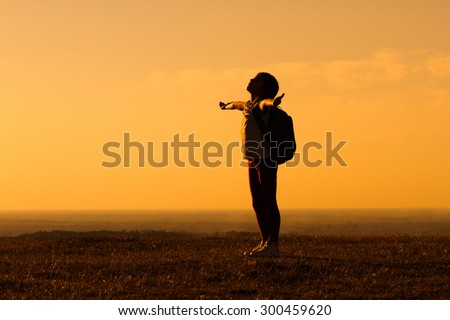Cute little hiker girl enjoys in sunset.Little hiker gretting the sunset - stock photo