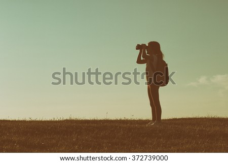 Cute little hiker girl looking with binoculars at sunset.Image is intentionally with grain and toned.Little hiker with binoculars - stock photo