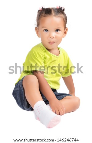 Cute little hispanic girl (toddler) sitting with a funny smile isolated on white