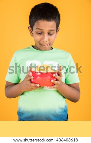 cute little indian boy eating chips or potato wafers, asian boy eating potato chips,  small boy eating chips in red bowl, over yellow background - stock photo