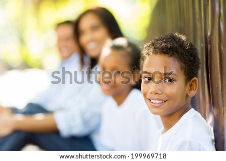 cute little indian boy sitting with family outdoors