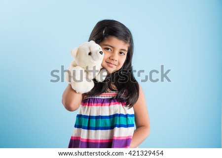 cute little indian girl playing with white soft toy puppet or puppet soft toy or puppet teddy bear isolated over blue background, asian small girl playing with puppet soft toy - stock photo