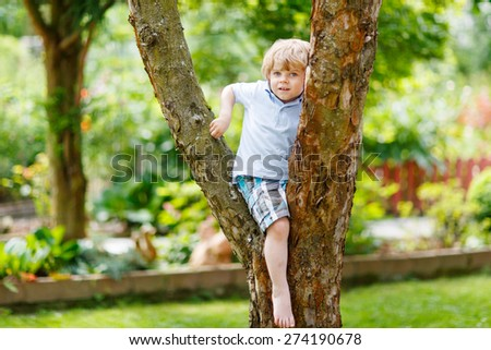 Cute little kid boy enjoying climbing on tree. Toddler child learning to climb, having fun in domestic garden on warm sunny day. - stock photo