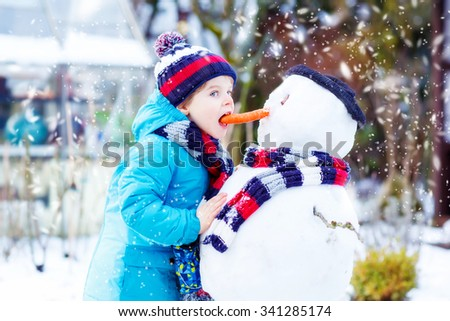 Cute little kid boy making a snowman and eating carrot. child playing and having fun with snow on cold day. Active outdoors leisure with kids in winter. - stock photo