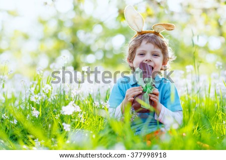 Cute little kid boy with Easter bunny ears celebrating traditional feast. Happy child  eating chocolate figure on sunny day. Family, holiday, spring , carefree childhood concept. - stock photo