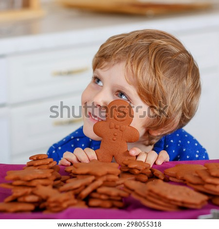 Cute little kid boy with fresh baked gingerbread cookies. Happy about gingerbread man. Kitchen decorated for Christmas - stock photo