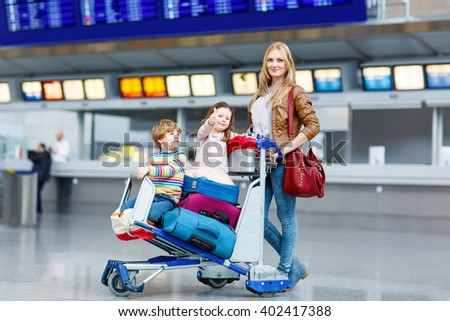 Cute little kid boy with red suitcase on international airport. Mother and daughter on background, happy family waiting for flight and going on vacations.